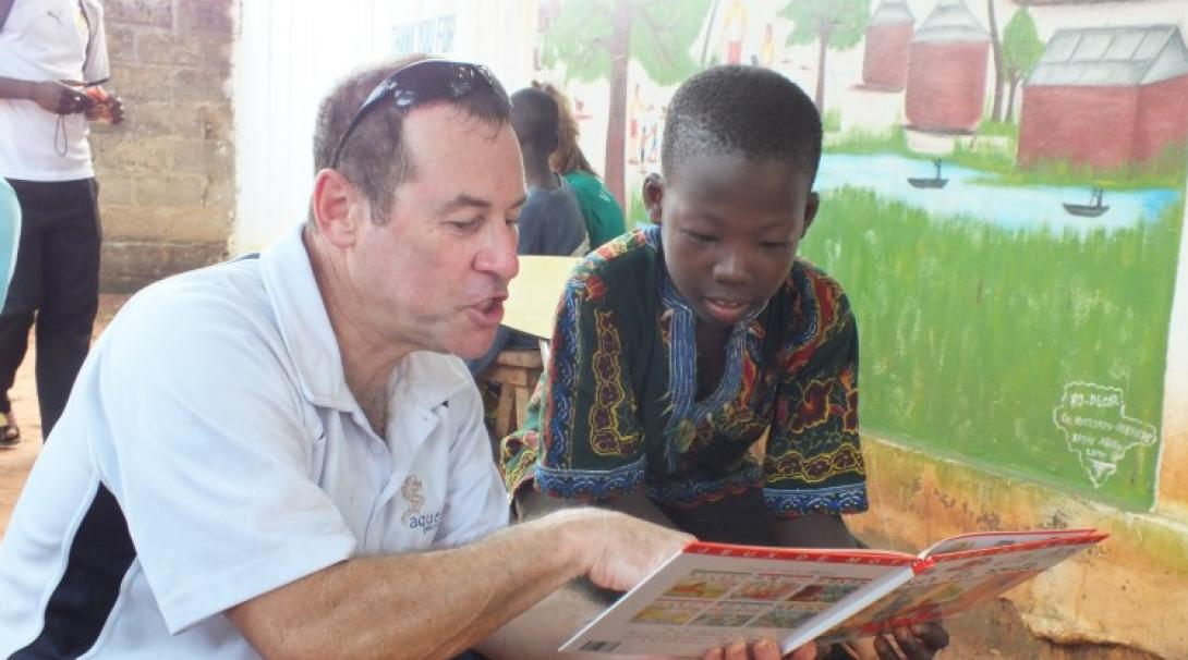 A male volunteer reads a book with a child